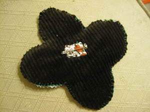 The brooch backing, bound on with a contrast fabric and blind stitch.