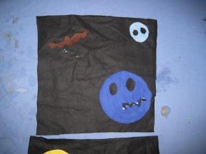 A bat, a big blue pumpkin and a spooooky moon with eyes